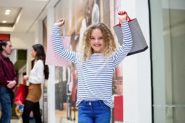Garota feliz, segurando sacolas de compras