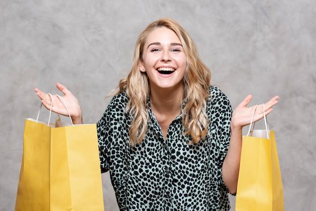 Garota feliz, segurando sacos de papel amarelo