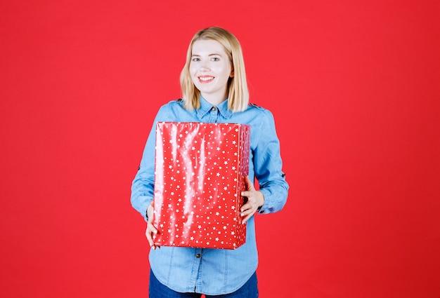 Garota feliz segurando um presente com as duas mãos em pé no vermelho