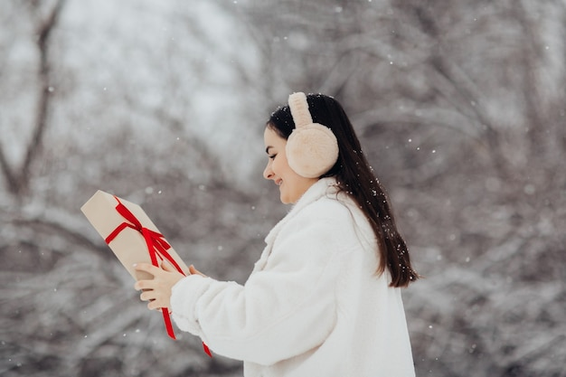 Garota feliz segurando uma caixa de presente com uma fita vermelha em um dia de inverno nevado para o dia dos namorados.
