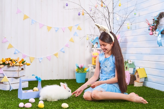 Garota feliz senta-se na grama com ovos pintados e alimenta coelho de estimação, no dia de páscoa