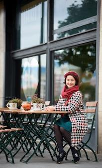 Garota feliz senta-se no café na rua de budapeste
