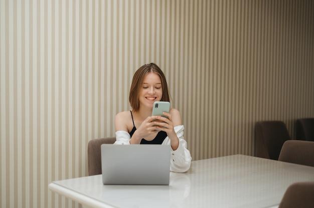 Garota feliz sentada em uma mesa em um apartamento com um laptop