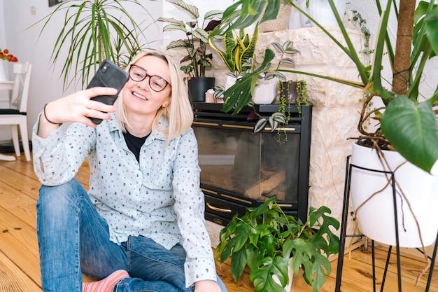 Garota feliz, sentado em casa cozinha e segurando videocall