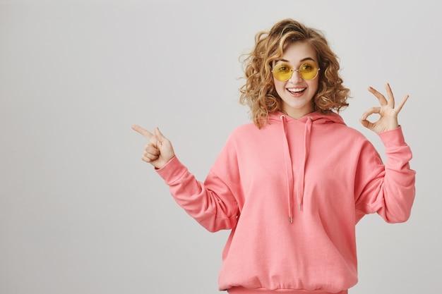 Garota feliz surpresa apontando para a esquerda, recomendar anúncio de produto, fazer gesto de aprovação