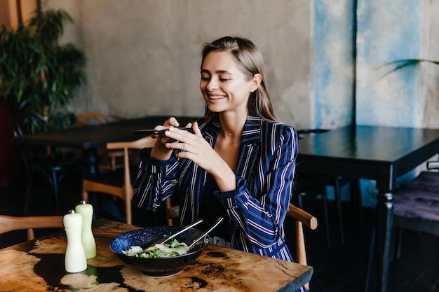 Garota feliz tirando foto de sua salada. retrato interior de mulher morena sorridente, se divertindo durante o jantar.