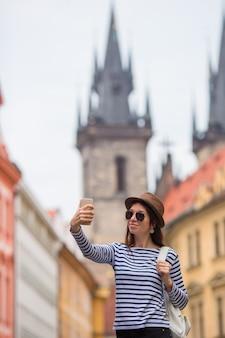 Garota feliz tomando selfie no famoso castelo na cidade europeia. caucasiana turista andando pelas ruas desertas