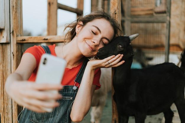 Garota feliz tomando uma selfie com uma cabra de bebê preto