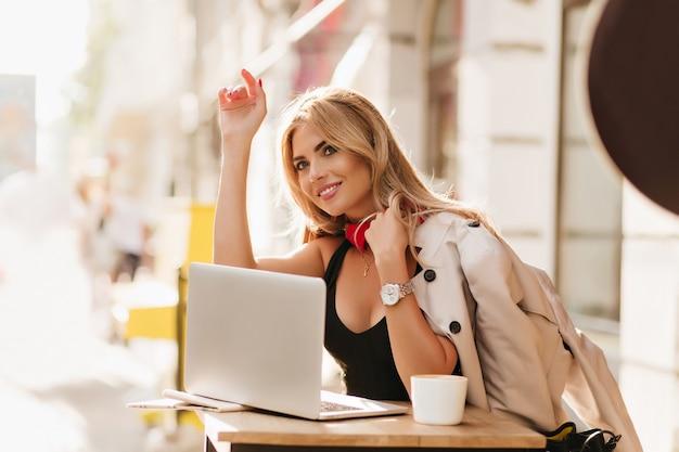 Garota feliz trabalhando com laptop em um café, acenando com a mão para um amigo e sorrindo