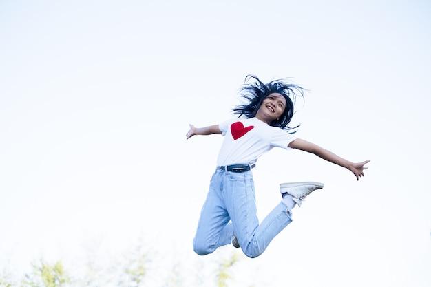 Garota feliz usa camisa branca e jeans pulando sobre fundo azul.