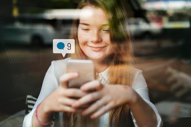 Garota feliz usando a mídia social em um smartphone em um café