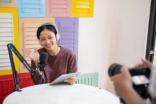 Garota feliz usando fones de ouvido na frente do gesto de saudação do microfone durante a abertura do podcast