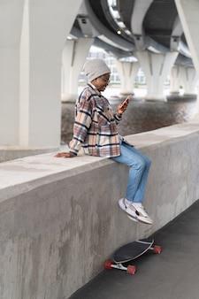 Garota feliz usando smartphone sorrindo, lendo mensagem de e-mail com conexão de internet sem fio g ao ar livre