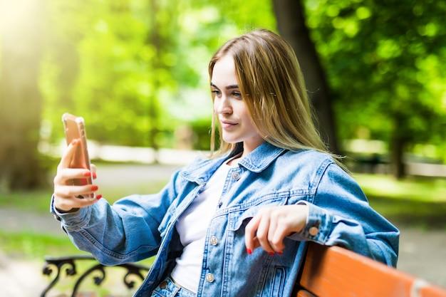 Garota feliz usando um telefone em um parque da cidade, sentado num banco