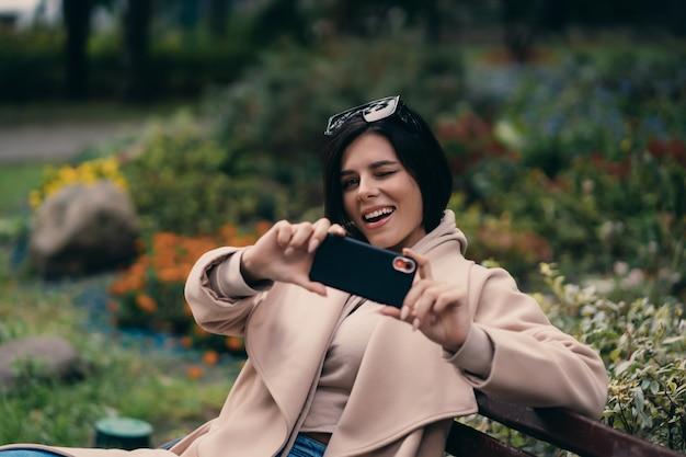 Garota feliz, usando um telefone inteligente em um parque da cidade, sentado num banco