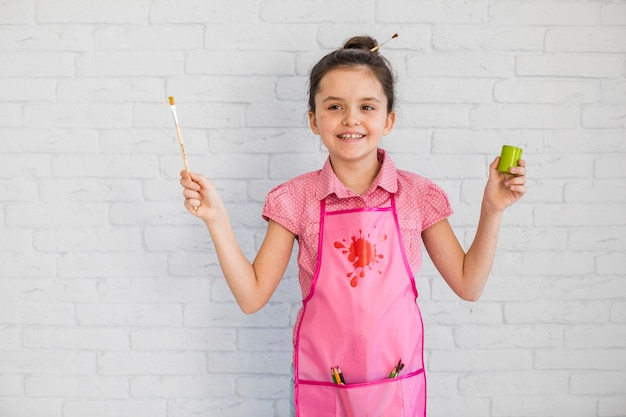 Garota feliz vestindo avental rosa segurando o pincel e a garrafa de tinta na mão