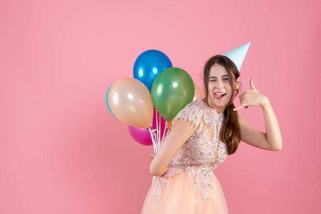 Garota festeira com boné segurando balões atrás das costas fazendo gesto de me ligar no telefone rosa