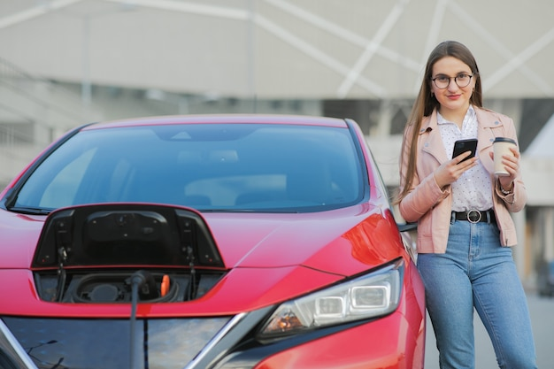 Garota fica com telefone perto de seu carro elétrico e aguarda quando o veículo será carregado. carregamento de carro elétrico