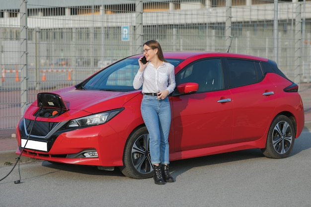 Garota fica com telefone perto de seu carro elétrico vermelho e aguarda quando o veículo será carregado. conectando o cabo de alimentação a um carro elétrico. carro ecológico conectado e carregando baterias