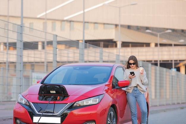 Garota fica com telefone perto de seu carro elétrico vermelho e aguarda quando o veículo será carregado. conexão do plugue do carregador de um carro elétrico