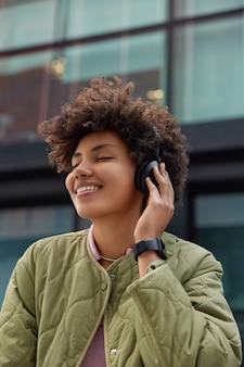 Garota fica de olhos fechados curtindo a melodia favorita em fones de ouvido sem fio sorrisos amplamente vestidos com jaqueta smartwatch no pulso