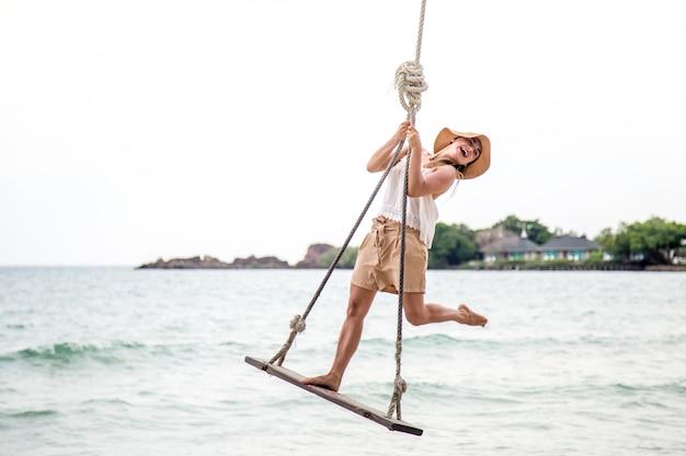 Garota fica em um balanço na praia da tailândia