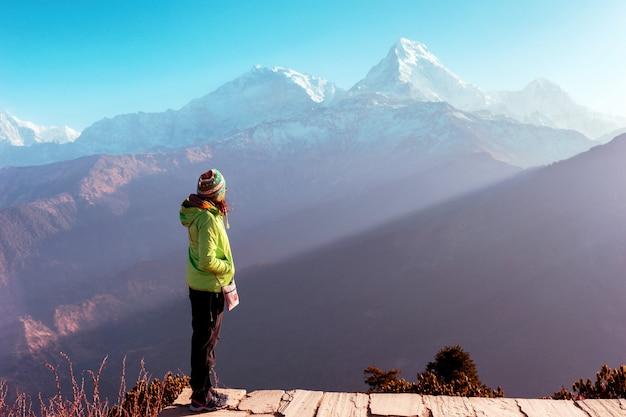 Garota fica em um fundo de montanhas cobertas de neve, himalaia, nepal