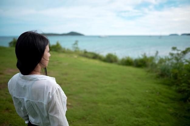 Garota fica em uma colina de costas e olha para o mar