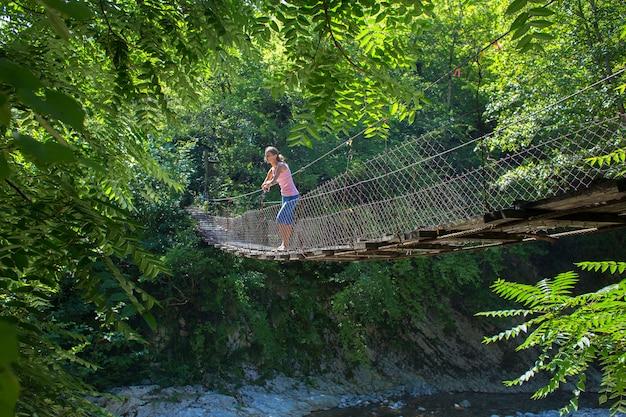 Garota fica na ponte de madeira suspensa sobre o rio da montanha e parece longe