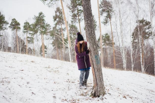 Garota fica perto de uma árvore, caminhada de inverno na floresta ou parque