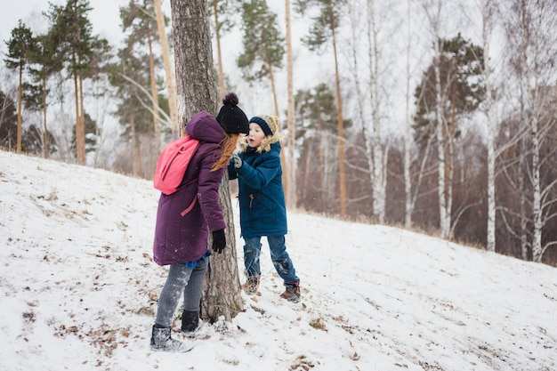 Garota fica perto de uma árvore com seu irmão mais novo, caminhada de inverno na floresta ou parque