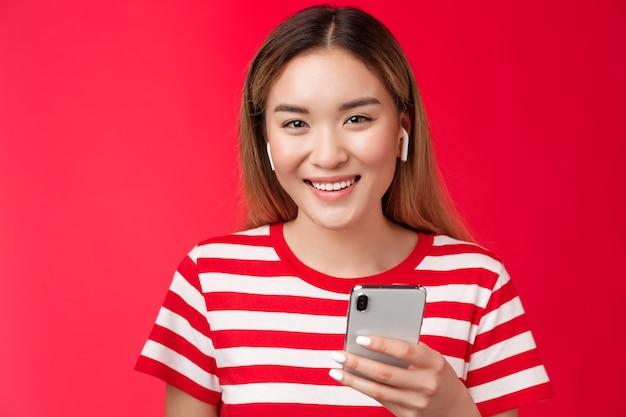 Garota ficando atenta assistindo vloggers favoritos usando fones de ouvido sem fio, sorrindo alegremente com os dentes da câmera ...