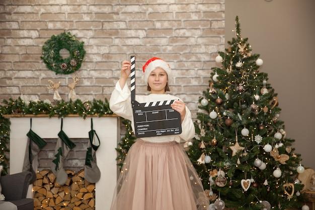 Garota filmando filme de natal na festiva sala de estar. foco suave