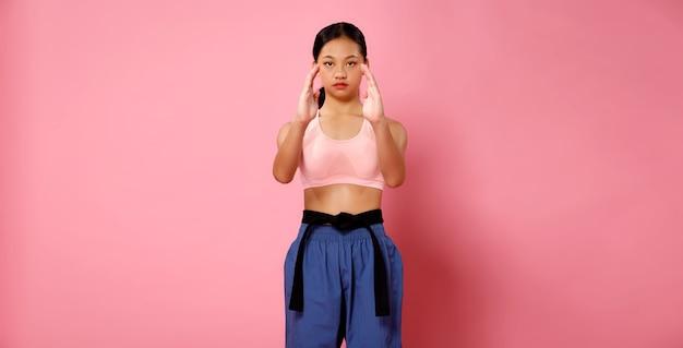 Garota fitness, a mulher pode fazer o conceito. atleta de 12 anos, comprimento total, mulher usa roupas esportivas em tons pastéis e pratica poses de luta sobre fundo rosa