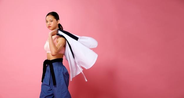 Garota fitness, a mulher pode fazer o conceito. atleta de 12 anos, comprimento total, mulher usa roupas esportivas em tons pastéis e uniforme sobre o ombro, fundo rosa, espaço de cópia