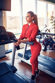 Garota fitness com agitador posando no ginásio