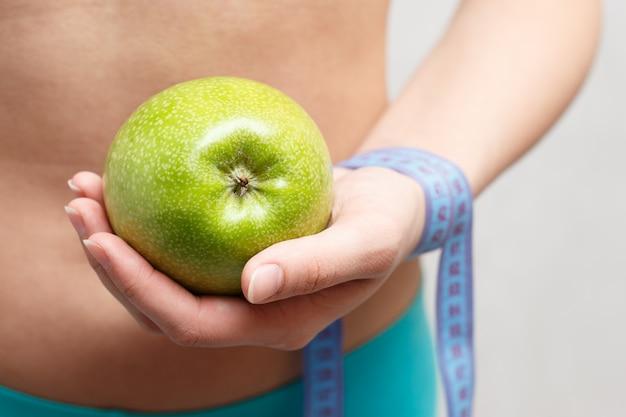 Garota fitness com centímetro e uma maçã na mão