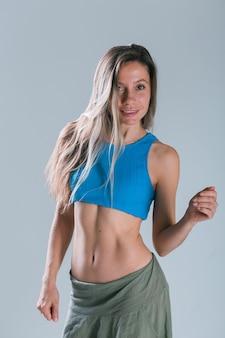 Garota fitness com corpo desportivo posando no estúdio em modelo sorridente de fitness de fundo cinza em