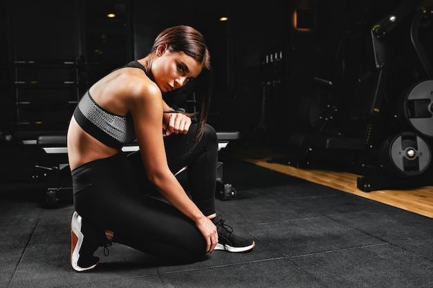 Garota fitness com escavadores posando em um banco no ginásio em roupas brilhantes, com um top branco e calças vermelhas. motivação fitness