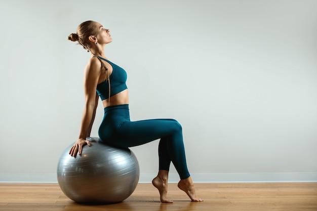 Garota fitness com fitball na sala de ginástica em fundo cinza. corpo kinky, flexibilidade e alongamento. copie o espaço.