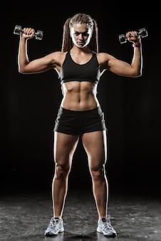 Garota fitness com halteres em um fundo escuro isolado