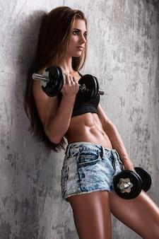 Garota fitness com halteres