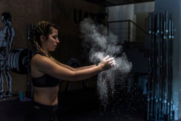 Garota fitness com poeira nas mãos dela