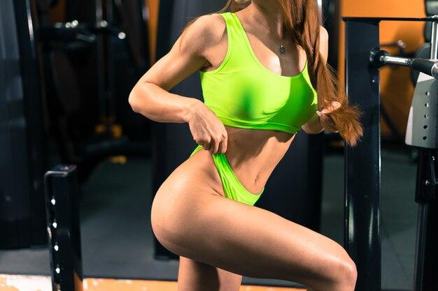 Garota fitness com um lindo sorriso, posando no ginásio