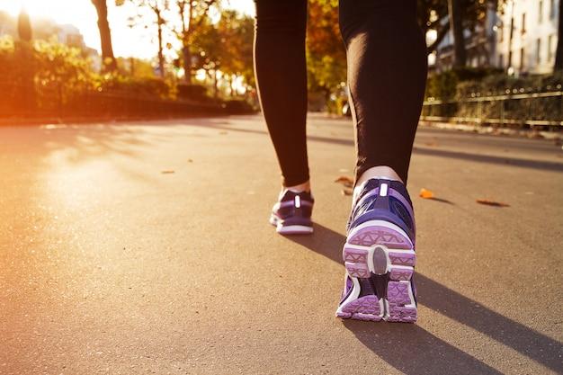 Garota fitness correndo ao pôr do sol