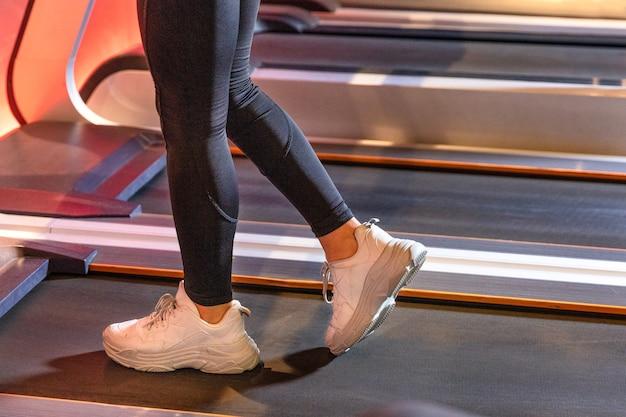 Garota fitness correndo na esteira com sapatos brancos