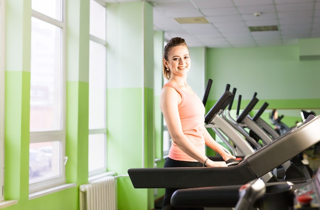 Garota fitness correndo na esteira. mulher com pernas musculosas no ginásio