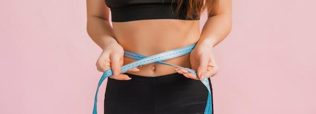 Garota fitness e mede a cintura em uma roupa esportiva preta em um espaço rosa