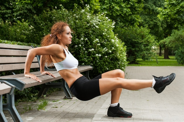 Garota fitness está malhando no parque