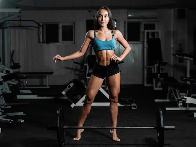 Garota fitness exercícios com barra, mulher posando no ginásio